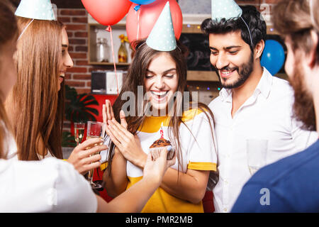 Friends congratulates brunette birthday girl in party hat with cupcake, she feeling surprised - Stock Photo