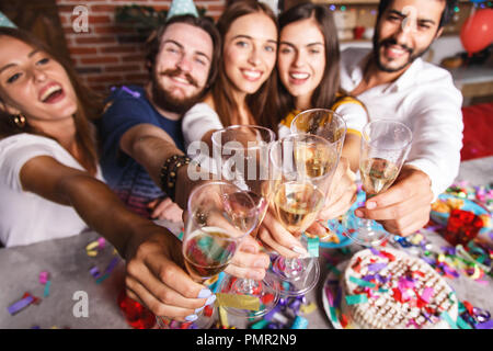 Attractive multicultural best friends laughing and raising glasses with champagne, they celebrating birthday party - Stock Photo