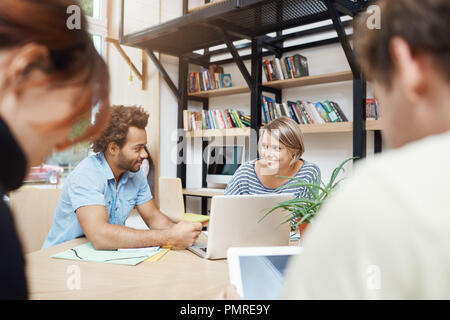 Close up of young designers team sitting in coworking space at table, talking about profits of old projects, looking through statistics on laptop, having conversation. - Stock Photo