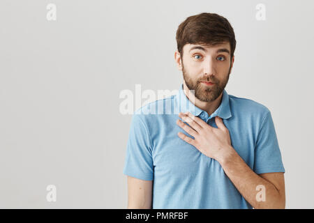 I feel like clearing my throat. Portrait of doubtful caucasian bearded guy holding palm on chest and looking with clueless or confused expression, coughing while being over gray background - Stock Photo