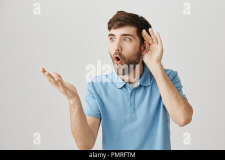 Indoor portrait of shocked and impressed guy holding hand near ear while overhearing gossip and gesturing as if he can not believe what he hears, looking aside with surprised expression. - Stock Photo
