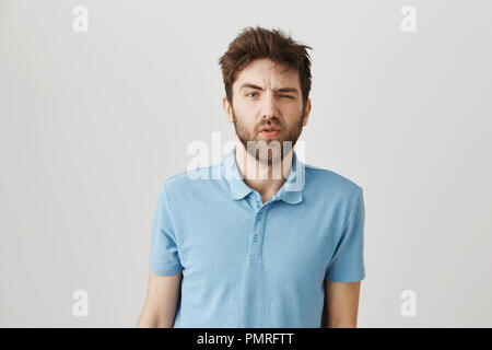 Slow down and tell again. Studio shot of messy sleepy bearded guy feeling puzzled and having no clue what is happening, awakening with hangover and standing over gray background. - Stock Photo