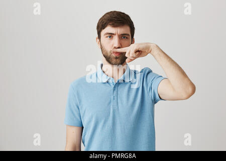 I do not want shave. Studio shot of positive funny european bearded male, standing with serious expression, frowning while holding index finger above nose as it is moustache over gray background - Stock Photo