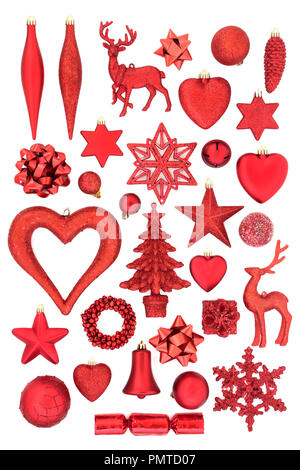 Red Christmas tree decorations, ornaments and symbols for the festive season on white background. Flat lay. - Stock Photo