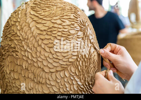 Caucasian artist working on her sculpture in an atelier - Stock Photo