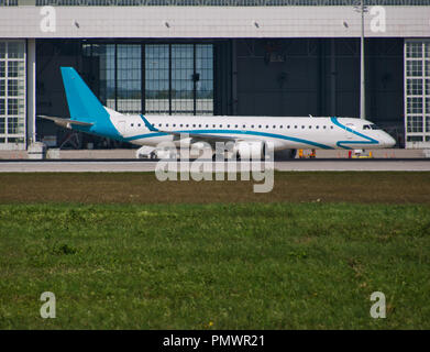 An airplane in front of the hangar with taxiway and a meadow in the foreground - Stock Photo