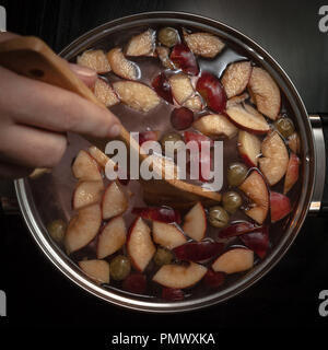 Stirring Colorful Apple Slices, Fruit Mix In A Pot With Wooden Spoon.  Refreshing Fruit Apple Cider Punch Party Drink. - Stock Photo