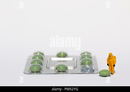 Small scientist in clean suit examining green pill from blister pack - Stock Photo