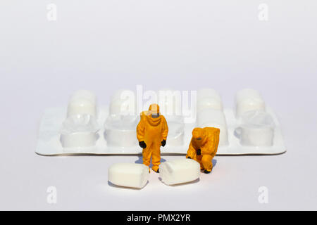 Small scientists in clean suits examining white tablet from blister pack - Stock Photo