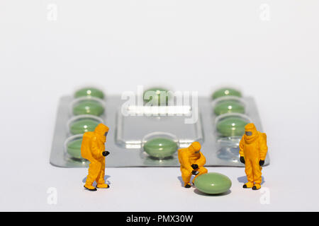 Small scientists in clean suits examining green pill from blister pack - Stock Photo