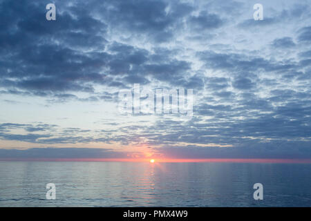 A glowing orange sun in the centre of frame just above the horizon line at sea. - Stock Photo