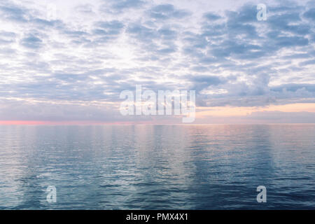 Reflections of the sky mirrored in an almost still and tranquil glassy sea/ ocean in the evening at sunset - Stock Photo