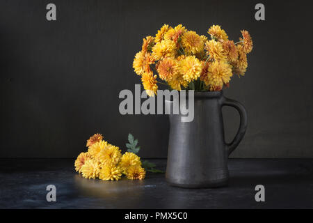 Autumn dark still life. Fall with yellow chrysanthemum flowers in clayware vase on black. Copy space. - Stock Photo