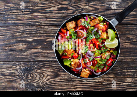 Texas caviar on a skillet. Fresh vegetables mix: bell pepper, tomatoes, black beans, corn, parsley, onion, sprinkled with lime juice with the addition - Stock Photo