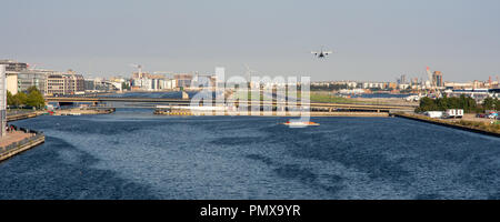 London, England, UK - September 2, 2018: A small passenger airplane flys low over Royal Victoria Dock on the approach to London City Airport in Dockla - Stock Photo
