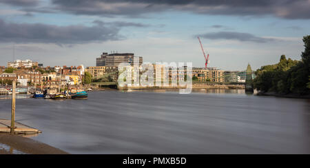 London, England, UK - September 9, 2018: Evening sun shines on Hammersmith Bridge and the River Thames riverside, including traditional houses, modern - Stock Photo