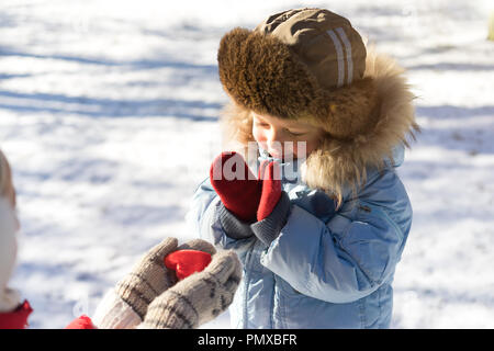 Woman holding red heart outdoor in the mittens and showing to small boy - Stock Photo