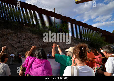 Protestors in Nogales, Sonora, Mexico, raise their fists to the border wall in Nogales, Arizona, USA, during a protest of the shooting of a teen in Me - Stock Photo