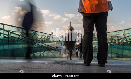 London, England, UK - April 20, 2010: Pedestrians cross the Millennium Bridge between Bankside and the City of London, with the dome of St Paul's Cath - Stock Photo