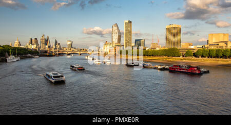 London, England, UK - June 12, 2018: Passenger ferries speed along the River Thames through central London, with skyscrapers of the South Bank and Cit - Stock Photo