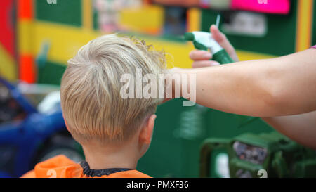 haircut of a little boy in a children's hairdressing salon - Stock Photo