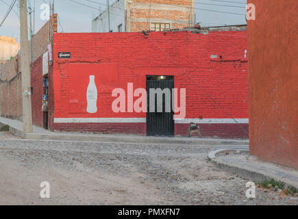 A store front with a red wall and a cola bottle painting in white, and a cobblestone street. On a street corner in San Miguel de Allende, Mexico. - Stock Photo