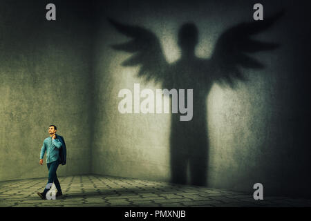 Proud and confident young businessman casting a superhero shadow with angel wings on a dark room wall. Inner power, ambition and leadership concept. - Stock Photo