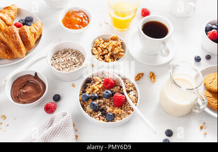 healthy breakfast with granola, berry, nuts, croissant, jam, chocolate spread and coffee - Stock Photo
