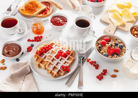 breakfast with granola berry nuts, waffle, toast, jam, chocolate spread and coffee - Stock Photo