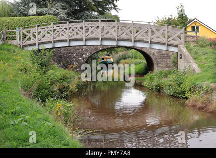 Stone Bridge over the Brecon and Monmouthshire canal in South Wales with narrowboat - Stock Photo