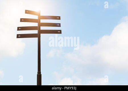 signpost guide direction sign on a pole with blue sky backgrounds - Stock Photo