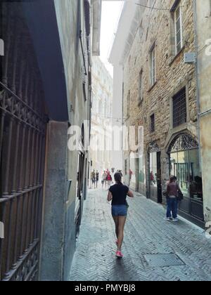Italy, Bergamo Altta. A young woman walks towards the old square, down a shaded narrow street - Stock Photo