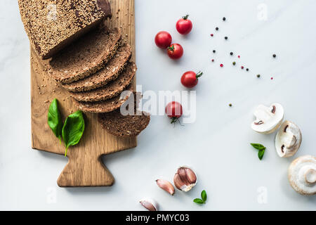 flat lay with cut bread on wooden cutting board, black pepper and vegetables for cooking breakfast on white marble surface - Stock Photo