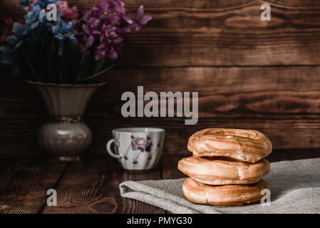 Eclairs stack on table with cup of coffee and vase of flowers - Stock Photo