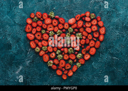 top view of heart sign made of ripe strawberries on blue concrete surface - Stock Photo