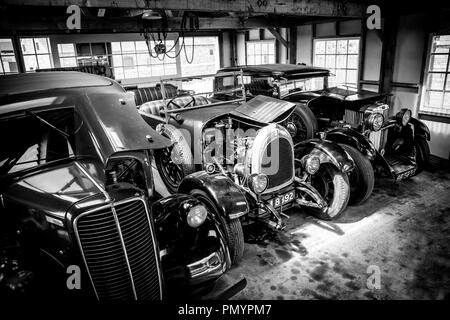 Arty, black and white, landscape shot of vintage classic cars parked, side by side, on display in an open garage space, taken from a high angle. - Stock Photo