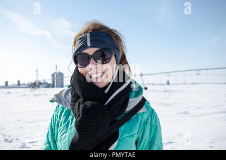 Attractive adult woman poses in farm field covered in snow on a cold winter day, wearing a ski jacket and hat - Stock Photo