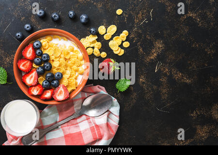 Dietary breakfast with cornflakes, milk and berries on a dark rustic background. The concept of healthy eating. Top view, copy space. Flat lay. - Stock Photo