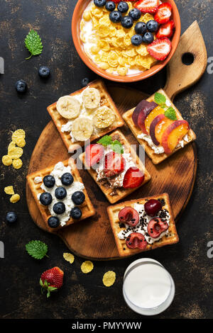 Fresh breakfast - corn flakes with milk and berries, homemade waffles with fruit on a dark background. The view from above, flat lay - Stock Photo