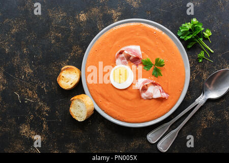 Traditional spanish andalusian tomato cream soup salmorejo served in a gray plate with ham and egg - Stock Photo