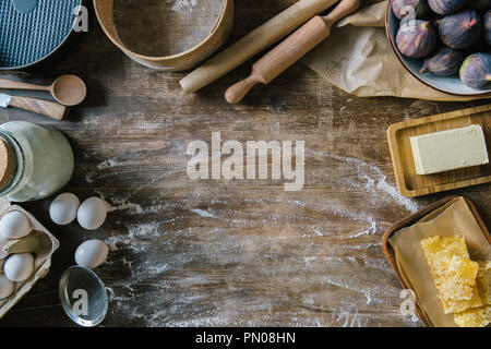 top view of messy wooden table with spilled flour and baking ingredients - Stock Photo