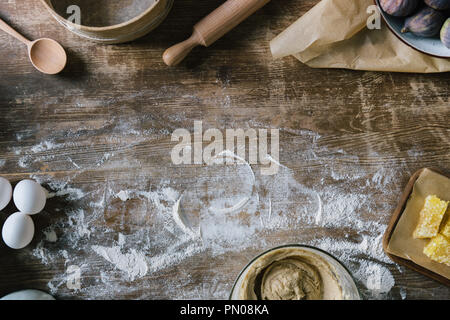 top view of messy rustic wooden table with spilled flour and baking ingredients - Stock Photo