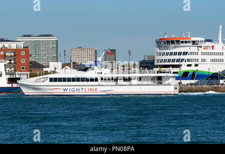 Isle of Wight fastferry Wight Rider 1 inbound Portsmouth Harbour, England UK, passing a new roro ferry on the quay. Victoria of Wight. - Stock Photo