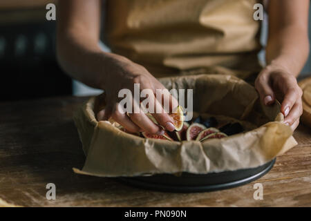 cropped shot of woman putting sliced figs into baking tray - Stock Photo