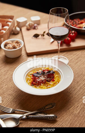 plate of delicious pasta with various ingredients and wine around on wooden table - Stock Photo