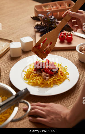 cropped shot of woman putting pasta in plate on wooden table - Stock Photo