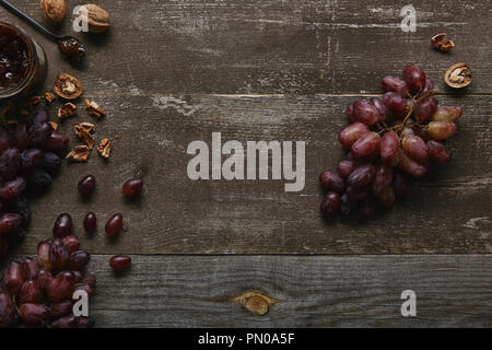 top view of fresh ripe grapes, walnuts and delicious jam on wooden table - Stock Photo
