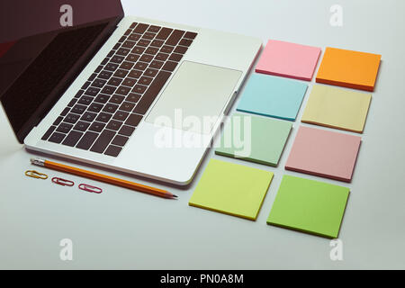 laptop, set of colored paper stickers, pencil and paper clips on white tabletop - Stock Photo