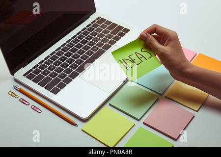 cropped image of woman holding paper sticker with word ideas near laptop - Stock Photo