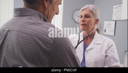 Doctor listening to patient's heart rate with stethoscope - Stock Photo